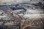 Alex MacLean: Bitumen is excavated at the Syncrude Mildred Lake mining site. Giant tires line the traffic circle.